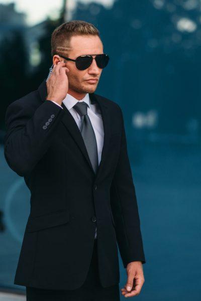 Male bodyguard uses security earpiece outdoors